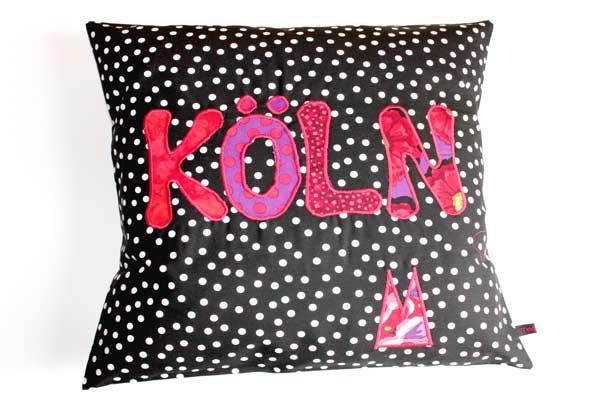 Köln-Kisssen - Rot-violette Schrift auf schwarz-weißen Tupfen